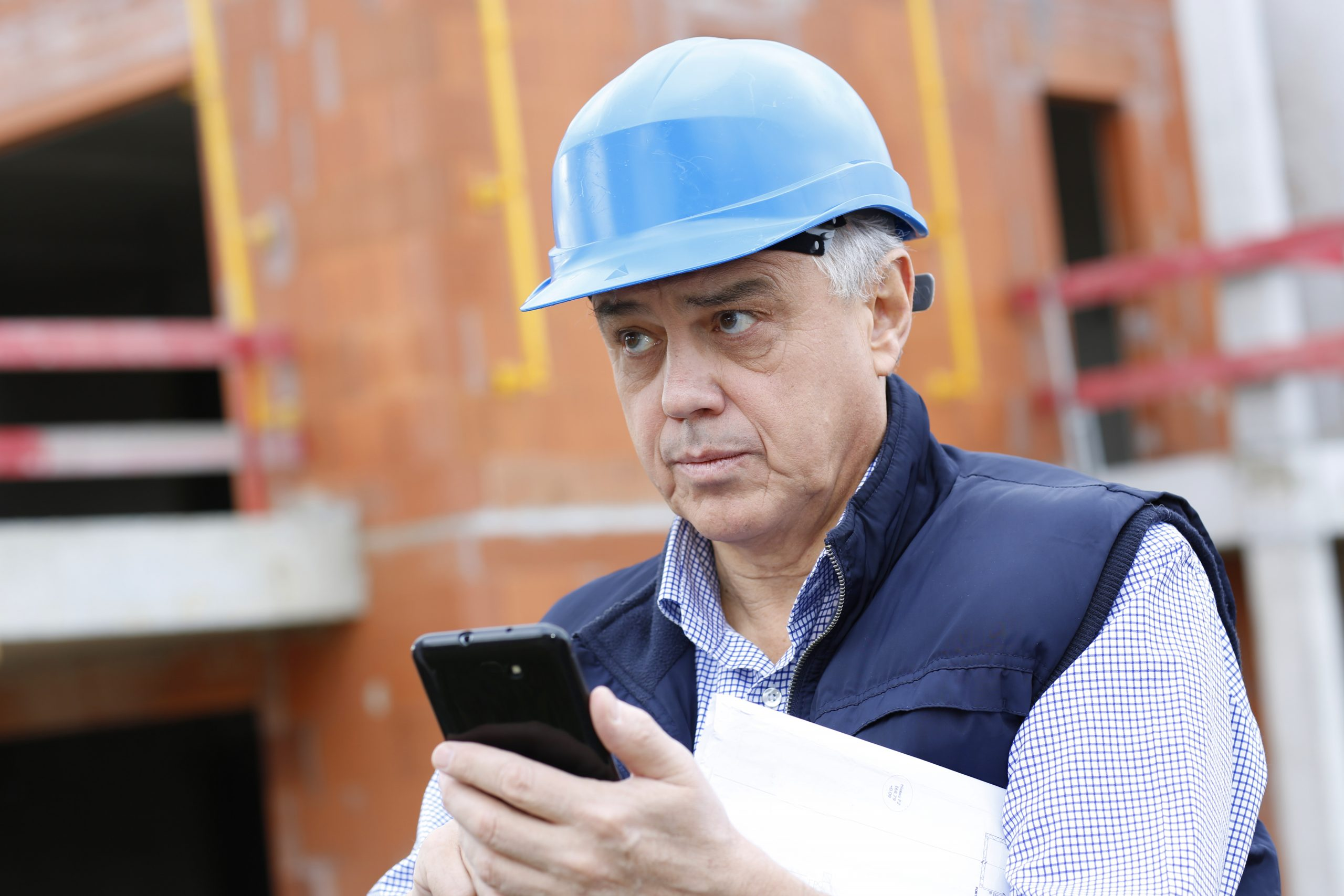 A man in a blue hard hat is looking at his mobile phone with a building site behind him
