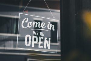 A door sign says 'come in we're open' in a shop door